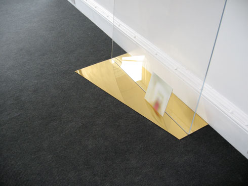 detail of sculptural arrangement gold mirrored perspex on floor with blurred image resting upright against a vertical plane of clear perspex