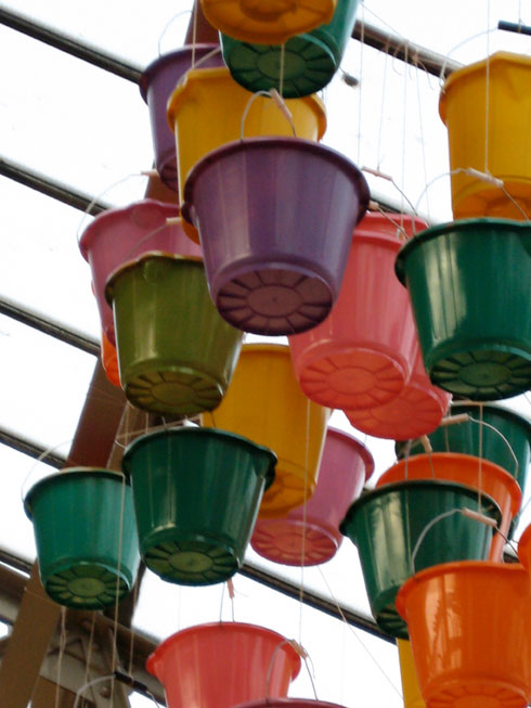 multicloured sprayed buckets hanging from glass ceiling of an old arm drill hall